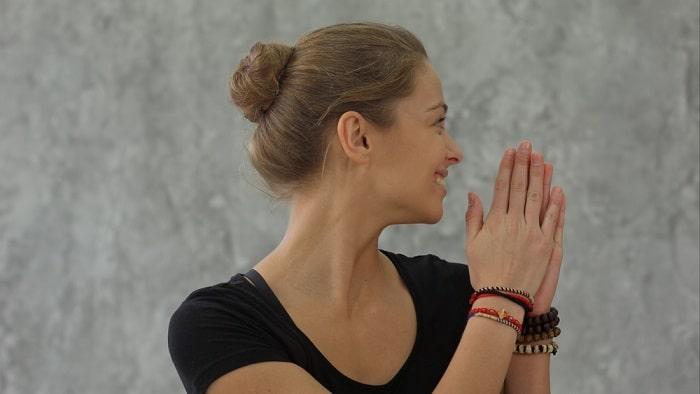 A female yoga instructor doing a namaste pose while smiling.