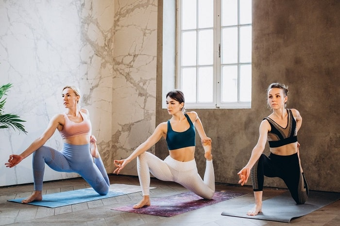 Three women balancing their bodies with an intermediate-level yoga pose on various colors of yoga mats inside a dance studio with marbled walls.
