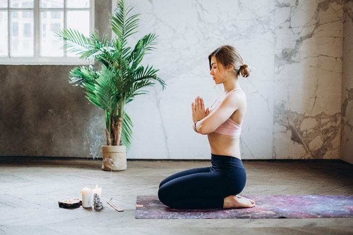 A woman in a sitting meditative yoga pose on a printed yoga mat with candles and incense in front of her.