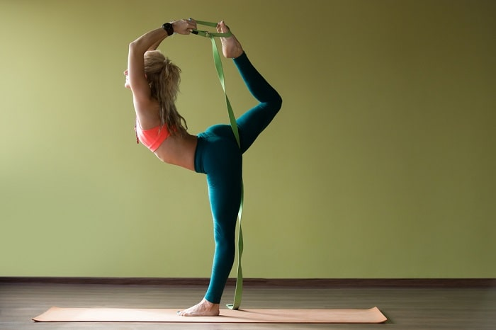 A woman in a standing pose with a green resistance band and an orange yoga mat inside a dance studio with yellow walls.