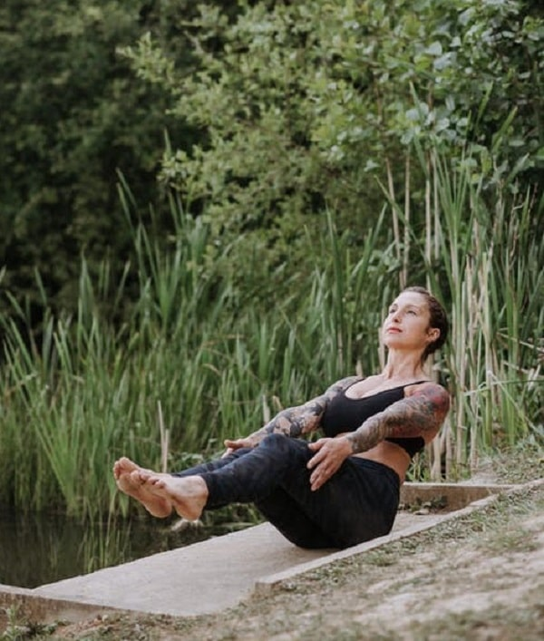 A woman doing Navasana or Boat Pose outdoors with some foliage in the background.