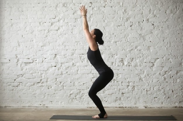 A woman doing Utkatanasa or Chair Pose on a dark gray yoga mat indoors with white brick walls.