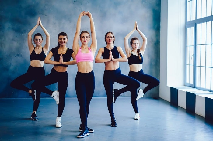 Women in various standing yoga poses beside a big window in a dance studio with concrete walls.