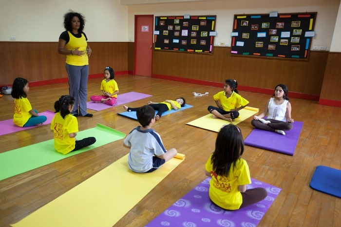 A female yoga instructor leading a kids yoga class at an indoor school gym.