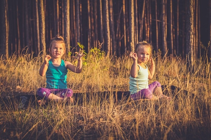 Two little girls practicing yoga on a sunny day outdoors.