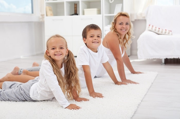 An adult woman doing a yoga pose with a girl and a boy on a white fluffy carpet.