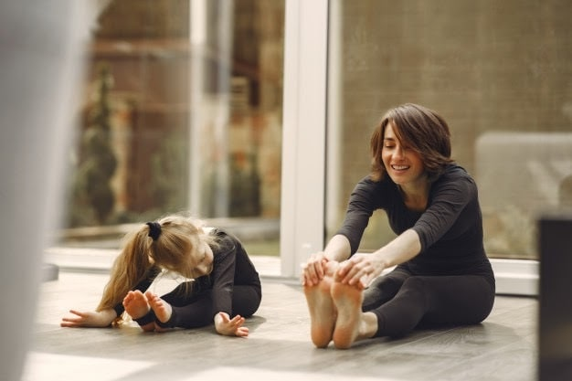 An adult woman teaching a young girl how to do a yoga pose on a wooden floor.