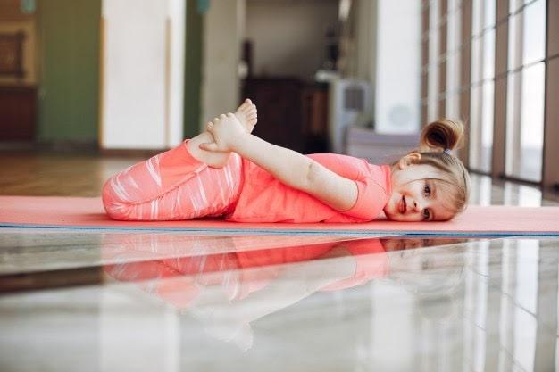 A little girl doing a yoga pose on her orange yoga mat.