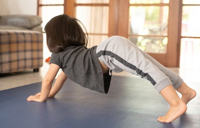 A preschooler doing a yoga pose on a gray mat indoors.