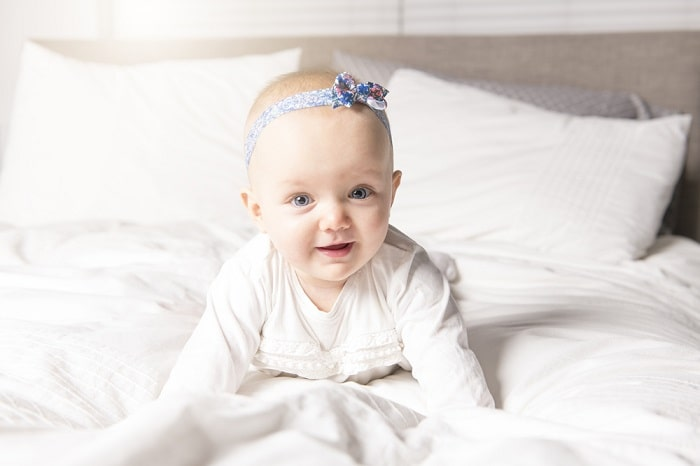 A baby girl on a bed, doing a Cobra Pose naturally.