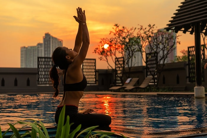A woman doing a sitting yoga pose by the poolside at sunset.