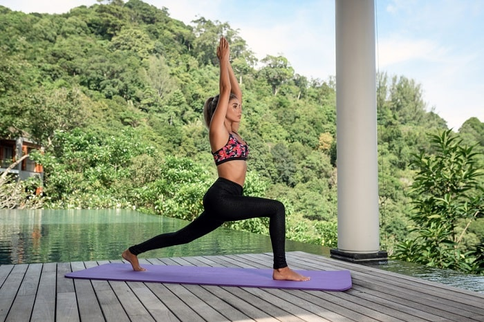 A woman practicing yoga on a purple yoga mat at a resort in the midst of nature.