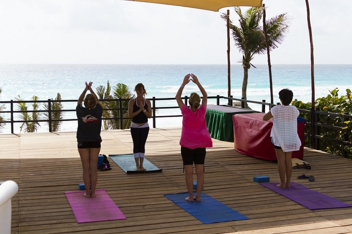 A female yoga instructor leading her students to do their yoga pose during a class at a resort, while facing the sea.