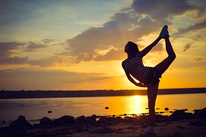 A woman doing her training exercises by the beach at sunset.
