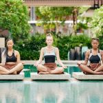 Three women in their swimsuits doing their yoga meditation beside the pool at a resort.