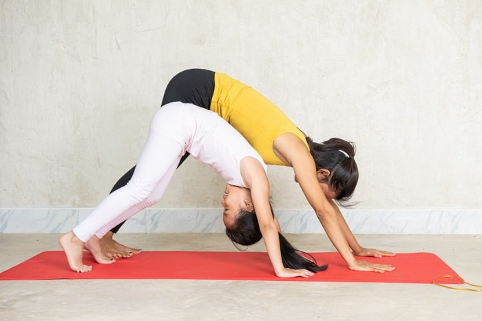 A mom and her daughter doing yoga on a red yoga mat, with the daughter smiling mid pose.
