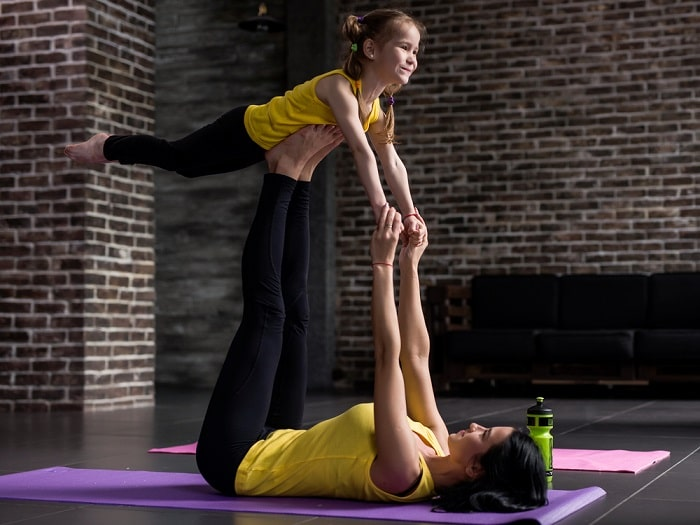 A mom and her daughter doing a partner yoga pose on a purple yoga mat indoors.