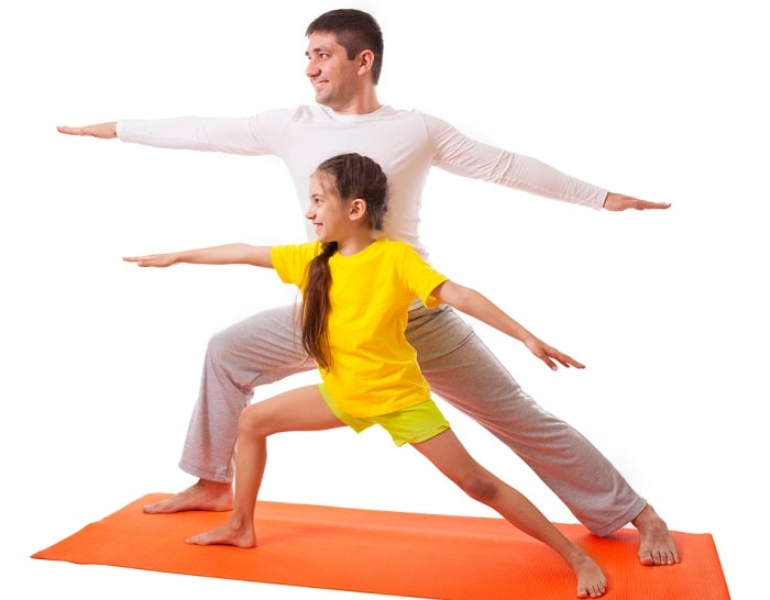 A dad and his daughter doing a standing yoga pose on an orange yoga mat.
