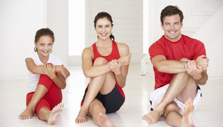 A family of three doing a yoga pose together.