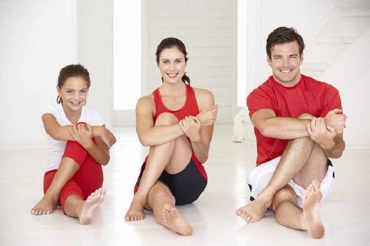 A family of three, with the mom, dad, and daughter doing the same sitting yoga pose together.