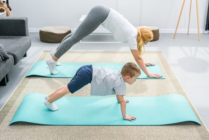 An adult woman teaching a young boy do a yoga pose on a blue yoga mat indoors.