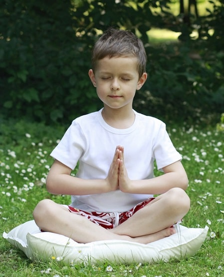 A boy in a meditative pose while doing yoga outdoors.