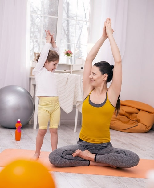 An adult woman showing a young girl how to do a yoga pose on an orange yoga mat indoors.