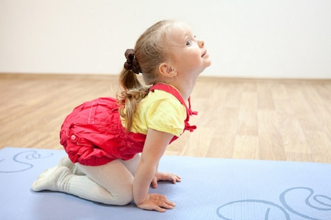 A young girl doing a freeze yoga pose on a printed yoga mat.