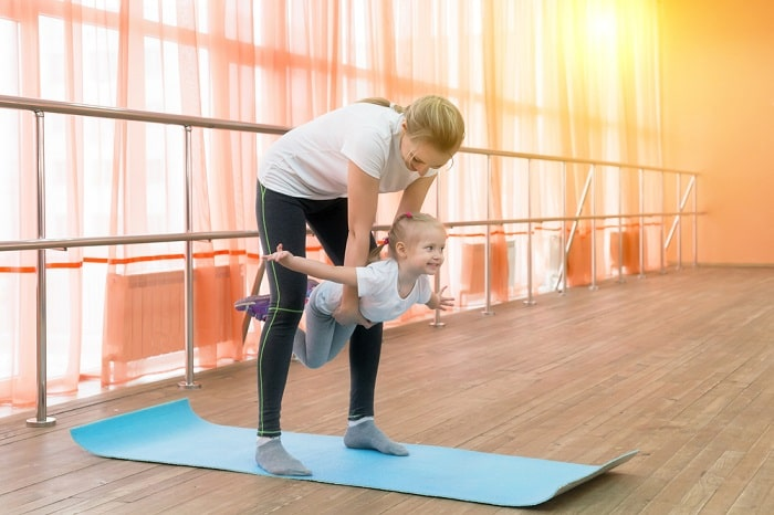 An adult woman lifting a young girl mid-yoga pose at an indoor gym.