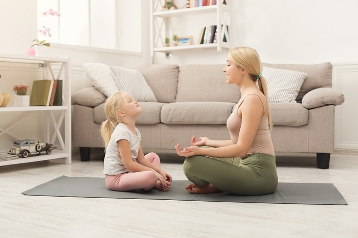 An adult woman teaching a young girl how to do yoga breathing exercises on a gray yoga mat.
