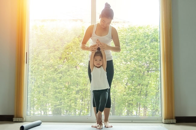 An adult woman teaching a young girl how to do Tree Pose during a yoga session indoors.