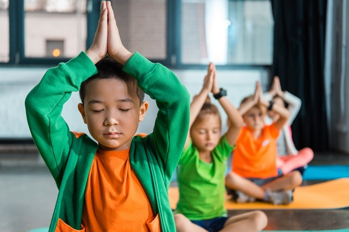 A group of preschoolers in a meditative yoga pose on their yoga mats indoors.