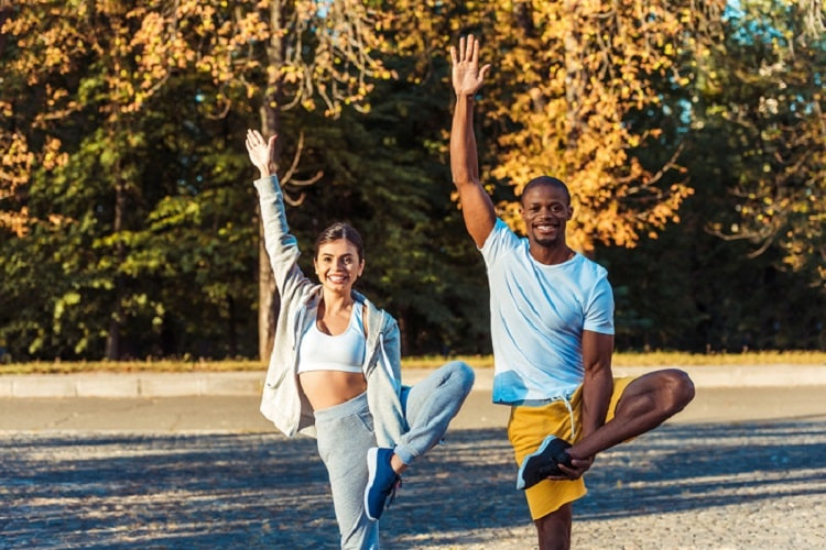 A woman and a man both smiling and doing a challenging standing yoga pose outdoors.
