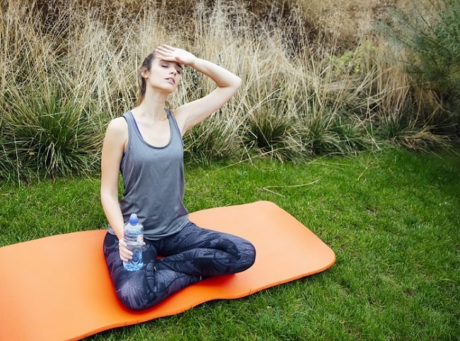 A woman wiping her forehead with one hand and holding a bottle of water in the other while sitting on an orange mat outdoors.