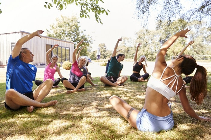 A female instructor leading an outdoor yoga class during a sunny day.