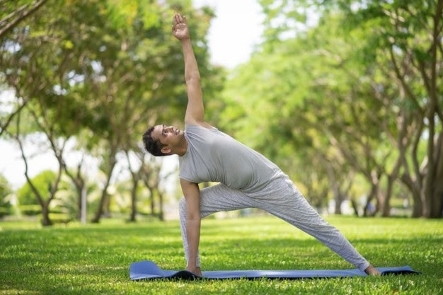 A man wearing grey exercise clothes while doing a yoga pose on a blue yoga mat placed on top of a grassy lawn.