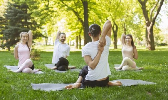 A yoga instructor teaching students how to do a yoga pose on their yoga mats in the park.