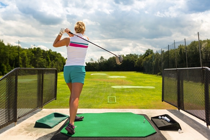 A female golfer practicing her golf swing while maintaining the proper form, facing a grassy golf course and clear skies above it.