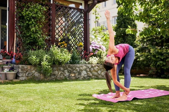 A woman doing Revolved Crescent Lunge on her pink yoga mat outdoors with a grassy lawn and some foliage in the background.