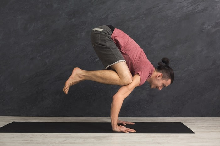 A man demonstrating flexibility and endurance while doing a difficult yoga pose on a black yoga mat indoors.