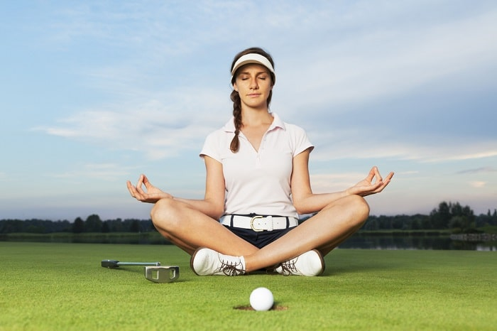 A female golfer in a sitting yoga pose, meditating on a golf course with both her golf ball and golf club placed on the grassy lawn.