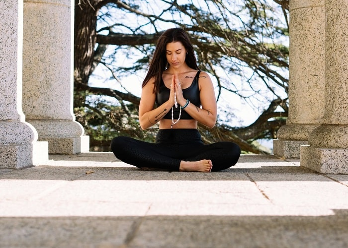 A woman with tattoos, holding her mala beads with hands pressed together while doing a sitting yoga pose outdoors.