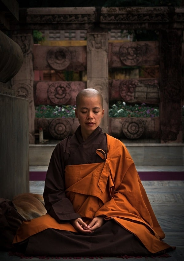 A monk in a brown and orange robe, meditating in silence at a temple.