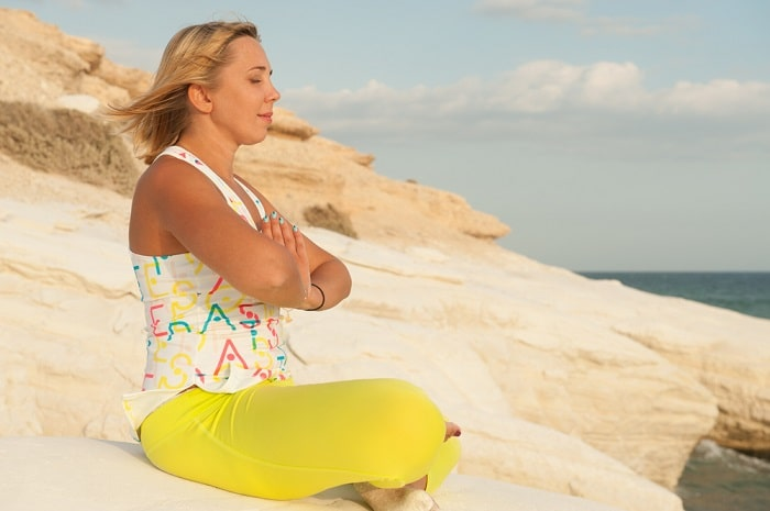 A woman in a printed top and yellow leggings with hands pressed together to her chest and eyes closed while meditating by the sea.
