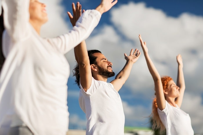 Yoga participants with their eyes closed and arms raised to the clear blue sky during a silent yoga retreat.