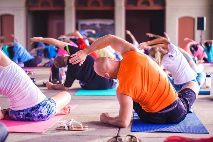 Students in a yoga class achieving their proper yoga pose on their yoga mats while inside a large venue.