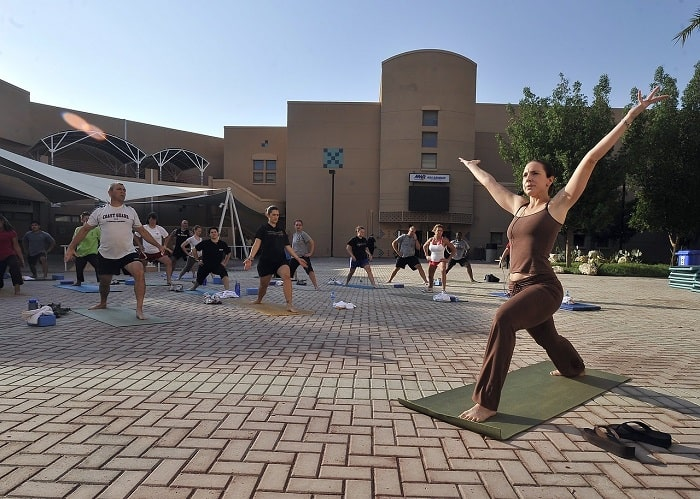 A female yoga instructor leading a group of people during a pop-up yoga class outside a large establishment.