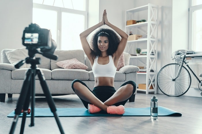 A woman doing a sitting yoga pose on her blue yoga mat indoors while facing the camera to shoot a video for social media.