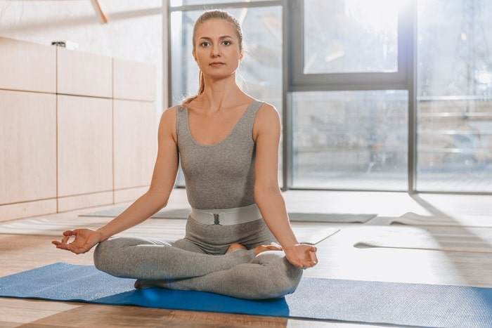A woman in a meditative yoga pose on her blue yoga mat, sitting inside an indoor studio.