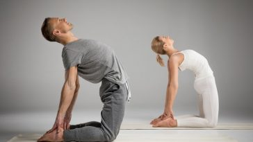 A man and a woman holding a yoga pose on their cream-colored yoga mats.
